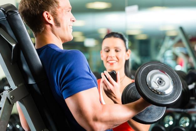 Personal trainer no ginásio e treino com halteres