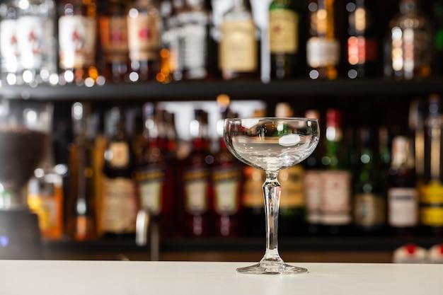 Perspectiva de close-up de baixo ângulo de vidro cupê vazio e cristalino no balcão do bar com desfoque