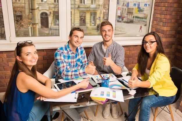 Perspectiva de freelancers de sucesso trabalhando com um projeto de negócios fazendo sinal de positivo