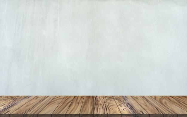 Perspectiva de madeira superior da tabela no fundo cinzento da parede do cimento.