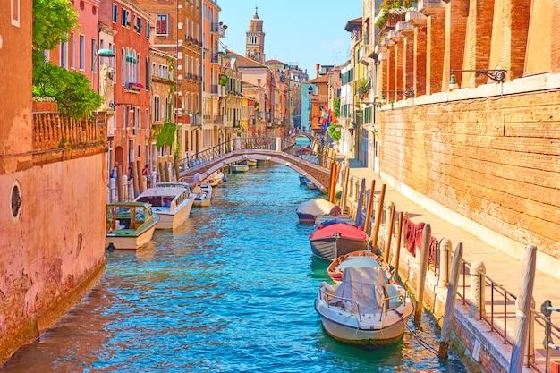 Perspectiva de um canal com barcos a motor atracados em veneza em um dia ensolarado de verão, itália