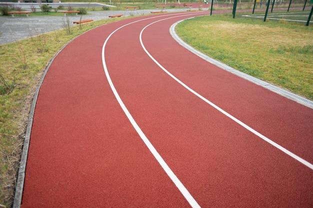 Perspectiva decrescente da pista de corrida do estádio com duas linhas dividindo-a em três seções