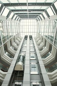 Perspectiva do saguão do escritório: telhado redondo e paredes de vidro em um corredor moderno com elevador