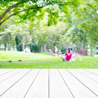 Perspectiva madeira branca mais desfoque abstrata árvores verdes folhas natureza com pessoas