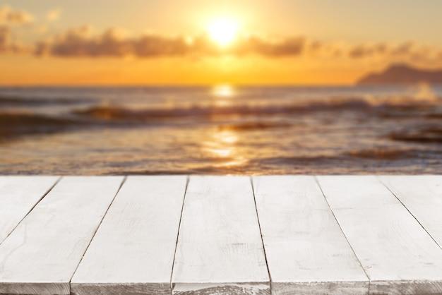 Perspectiva vazia, tábuas de madeira brancas ou bancada contra vista do mar turva com pôr do sol no fundo. use como modelo e maquete para exibição ou montagem de seus produtos. close up, copie o espaço