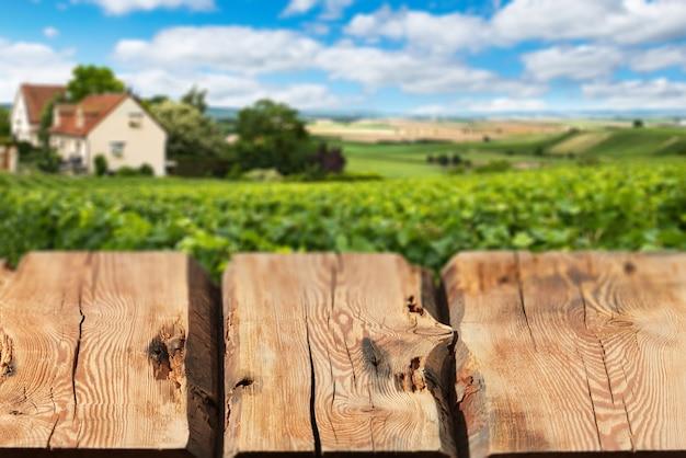Perspectiva vazia, tábuas de madeira não tratadas ou bancada contra a paisagem turva do campo no fundo. use como modelo para exibição ou montagem de seus produtos, publicidade. close up, copie o espaço