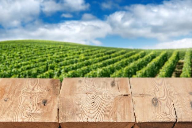 Perspectiva vazia, tábuas de madeira não tratadas ou tampo da mesa contra vinhedo verde turva sob o céu azul em fundo. use como maquete para exibição ou montagem de seus produtos. close up, copie o espaço