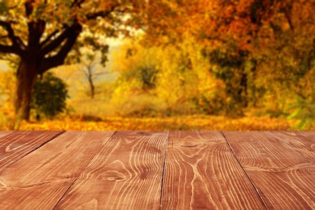 Perspectiva vazia, tábuas de madeira ou área de trabalho contra paisagem turva da floresta de outono no fundo. use como modelo e maquete para exibição ou montagem de seus produtos, publicidade. close up, copie o espaço