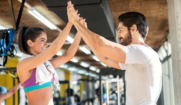 Perto da adorável garota jovem fitness de mãos dadas com o personal trainer e comemorando o progresso no ginásio.