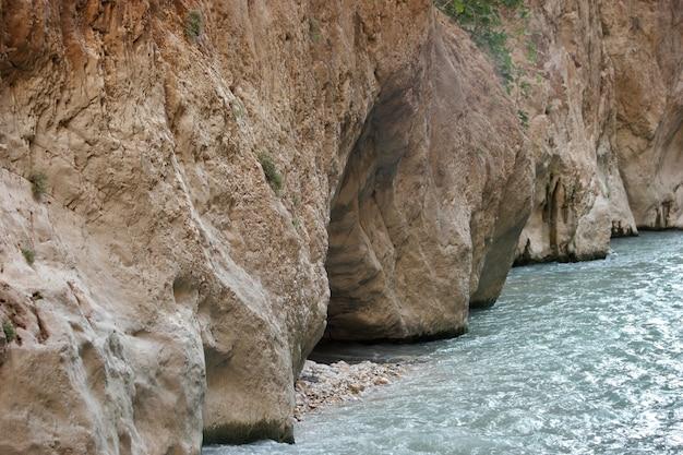 Perto da água fluindo através de formações rochosas. penhasco de arenito e águas claras do rio.