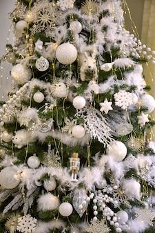 Perto da árvore de natal com enfeites brancos de bugigangas