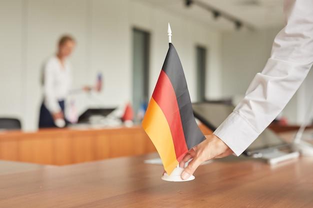 Perto da assistente feminina colocando a bandeira alemã na mesa enquanto prepara a sala de conferências para um evento internacional de negócios.
