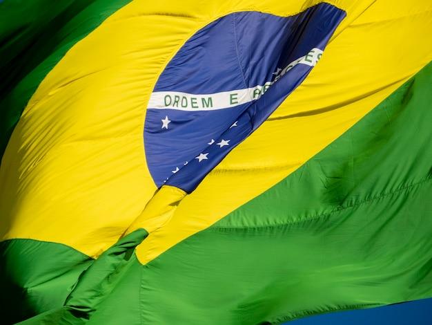 Perto da bandeira brasileira tremulando ao vento. no centro da bandeira com as palavras
