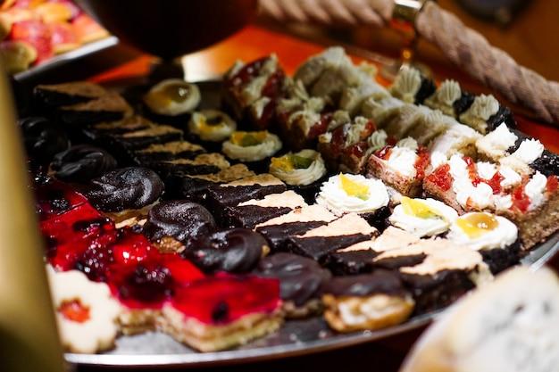 Perto da bandeja com tortinhas de bolos deliciosos em uma fileira. sobremesas doces de frutas frescas e coloridas, lindamente decoradas