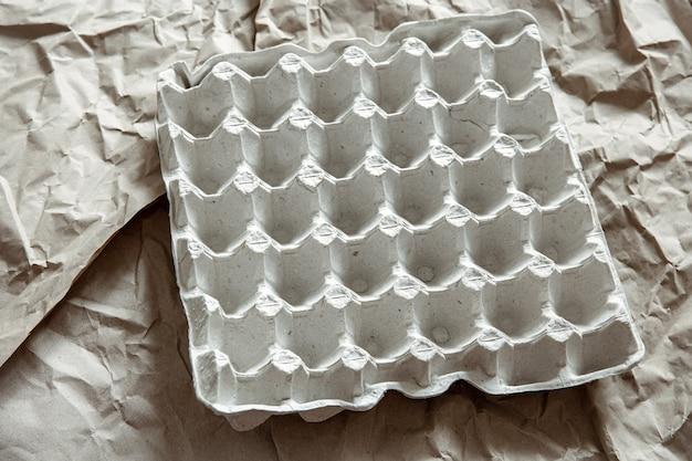 Perto da bandeja de ovos vazia de papel amassado. o conceito de reciclagem, reutilização.