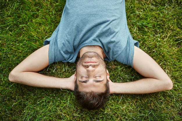 Perto da bela barbudo homem caucasiano maduro em t-shirt azul deitada na grama em noite de verão com os olhos fechados e expressão facial relaxada.