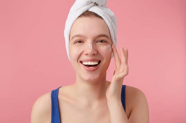 Perto da bela jovem sorridente com beleza natural com uma toalha na cabeça depois do banho, olhando e coloca creme facial.