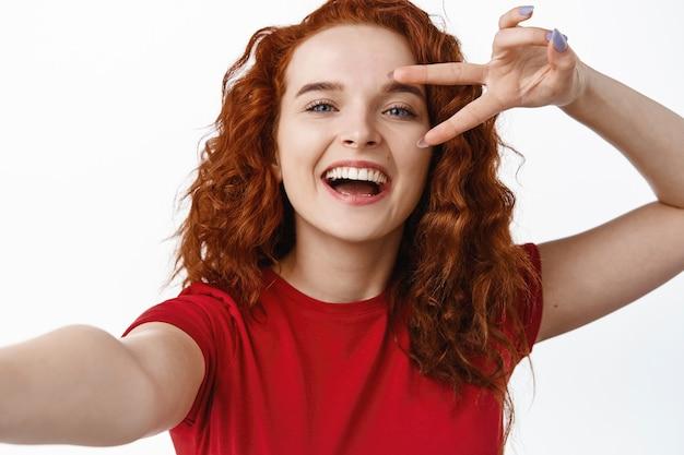 Perto da bela ruiva sorridente, mostrando o sinal v e rindo, tirando uma selfie, segurando o smartphone na mão estendida, parede branca