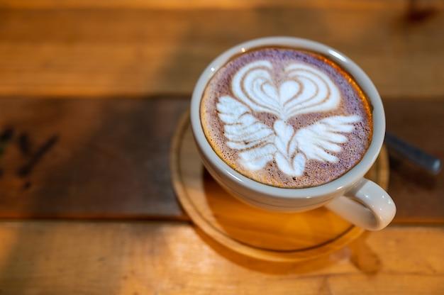 Perto da bela xícara de café latte art na mesa de madeira