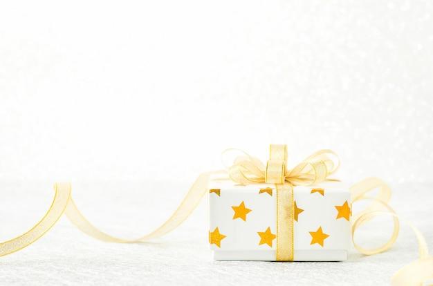 Perto da caixa de presente branca com padrão de estrela dourada e laço de fita de ouro