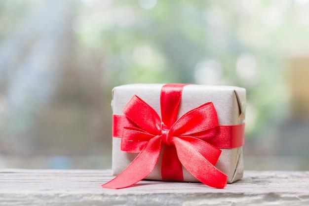 Perto da caixa de presente de artesanato com fita vermelha para o natal em luzes desfocadas