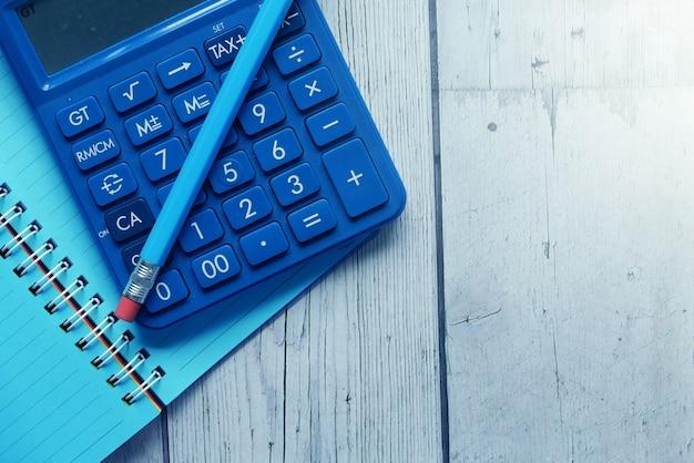Perto da calculadora azul e do bloco de notas na cor de fundo