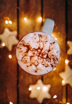 Perto da caneca branca de natal com chocolate quente, chá ou café e marshmallow. conceito de época de inverno e natal.