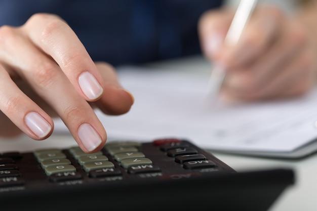 Perto da contadora ou banqueiro fazendo cálculos. conceito de economia, finanças e economia