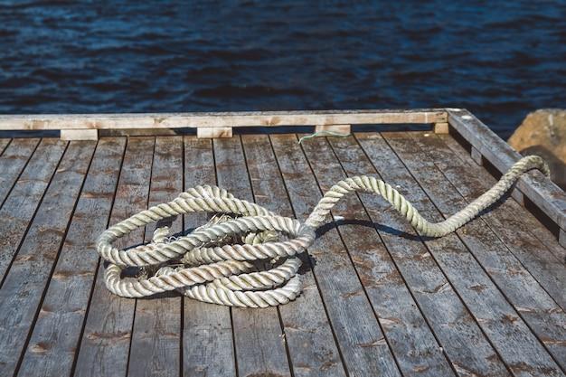 Perto da corda de amarração grossa desgastada no cais de madeira. pode usar como banner.
