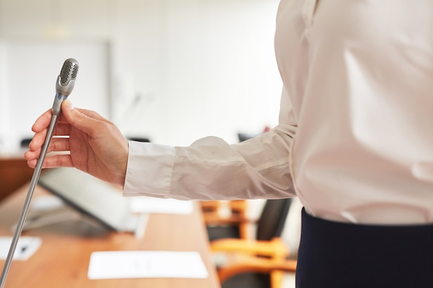 Perto da elegante secretária feminina ajustando o microfone enquanto prepara a sala de conferências para o evento de negócios,