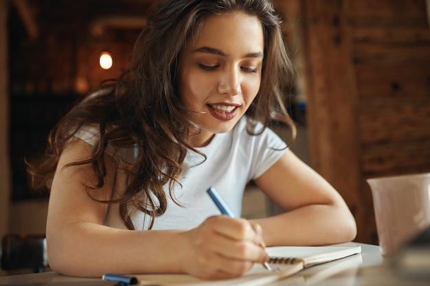 Perto da encantadora adolescente plus size com cabelos soltos ondulados, sentada na mesa com o caderno, caligrafia, desenhando ou fazendo esboços, tendo o olhar alegre. conceito de criatividade, hobby e lazer