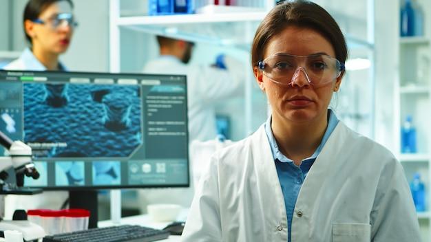 Perto da enfermeira cientista parecendo cansado para a câmera, sentado no moderno laboratório equipado, tarde da noite. equipe de especialistas examinando a evolução do vírus usando alta tecnologia para pesquisa e desenvolvimento de vacinas