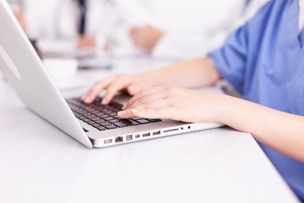 Perto da enfermeira médica digitando no laptop durante a reunião de healtchare com colegas de trabalho na sala de reuniões do hospital. terapeuta especialista em clínica falando com colegas sobre doenças, profissional de medicina