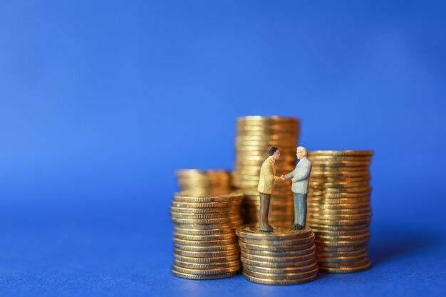 Perto da figura de miniaturas de empresários em cima da pilha de moedas de ouro