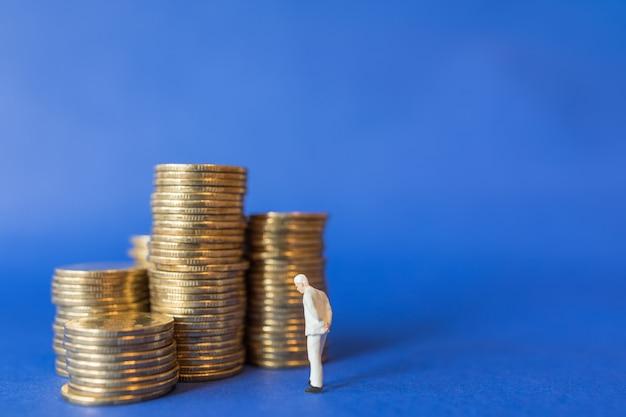 Perto da figura de pessoas em miniatura do empresário em pé com uma pilha de moedas de ouro