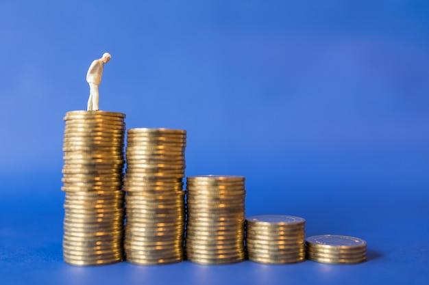 Perto da figura em miniatura do empresário em cima da pilha de moedas de ouro