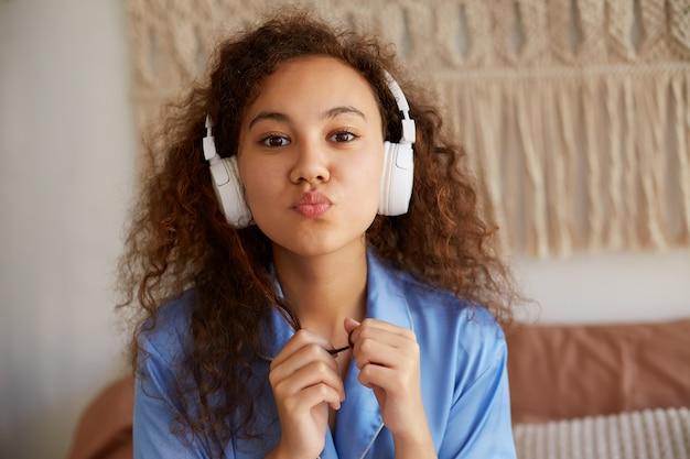 Perto da fofa encaracolado afro-americano jovem ouvindo música romântica favorita em fones de ouvido, manda um beijo, parece feliz.