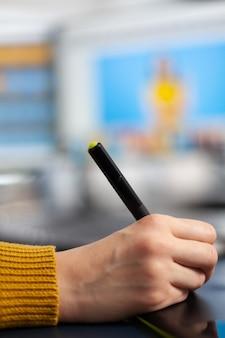 Perto da foto de uma jovem desenhando em um tablet gráfico, editando a foto do cliente