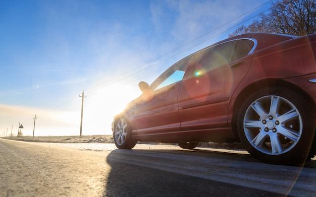 Perto da frente do novo carro vermelho na estrada de asfalto em um dia ensolarado