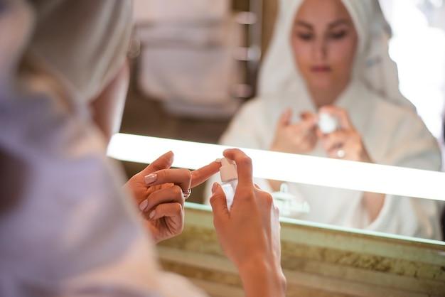 Perto da garota aplicando creme cosmético no dedo. visão turva do espelho com o rosto de uma jovem mulher europeia bonita usar roupão de banho e toalha de banho enrolada na cabeça. conceito de cuidados com a pele do rosto