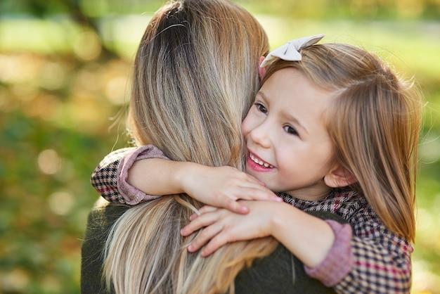Perto da garota feliz abraçando a mamãe