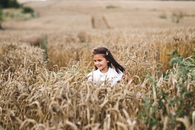 Perto da garota feliz com longos cabelos loiros, correndo para a câmera através do campo de cevada.