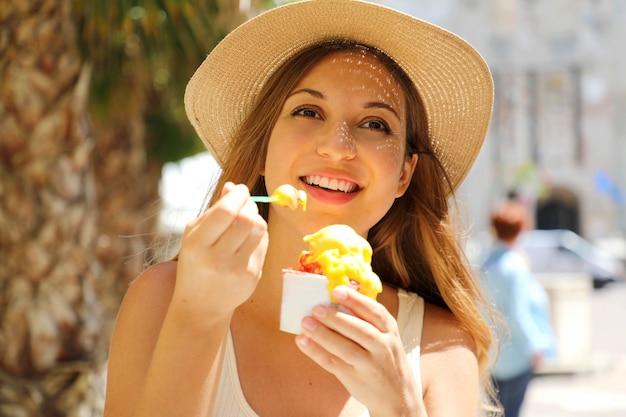 Perto da garota turista comendo sorvete tradicional italiano sorvete na cidade de sirmione, itália. jovem mulher com chapéu segurando sorvete, apreciando olhar para o lado em suas férias na europa.