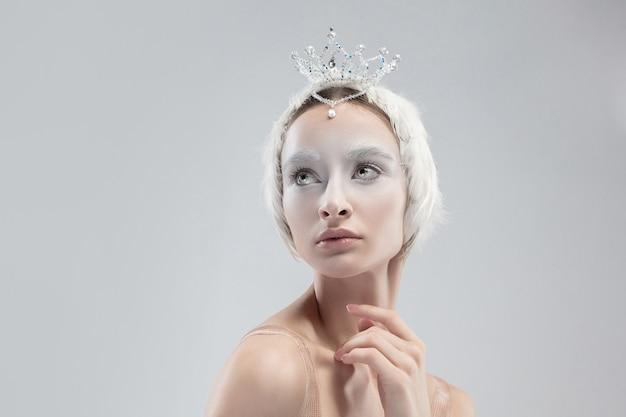 Perto da graciosa bailarina clássica em fundo branco do estúdio. mulher com roupas macias, como um personagem de cisne branco. o conceito de graça, artista, movimento, ação e movimento. parece leve.