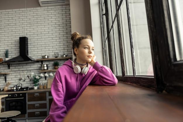 Perto da janela. adolescente fofa e atraente sentindo-se melancólica sentada perto da janela em casa