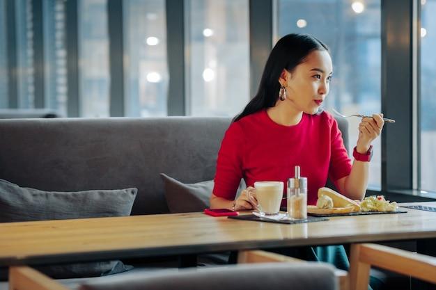 Perto da janela mulher jovem e elegante de cabelos escuros sentada perto da janela de um restaurante