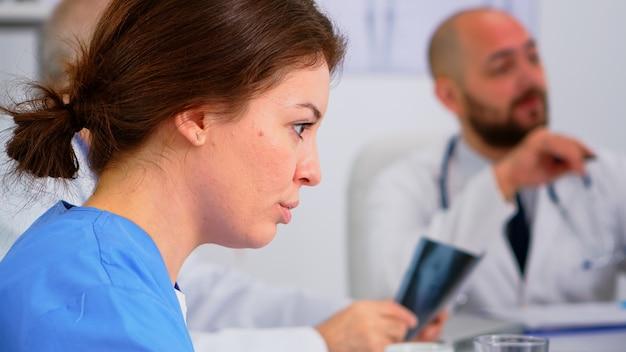 Perto da jovem enfermeira discutindo com o colega durante a conferência médica, sentado na mesa no escritório de reuniões do hospital. falando sobre os sintomas da doença na clínica durante o brainstorming
