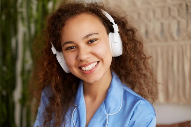 Perto da jovem mulata encaracolada feliz, amplamente sorri e ouvindo a música favorita em fones de ouvido, curtindo a música e os domingos de manhã.