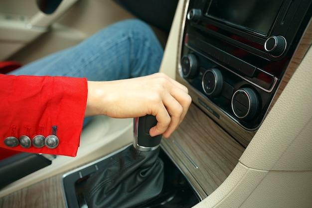 Perto da jovem mulher trocando as marchas da caixa de marchas e dirigindo o carro.