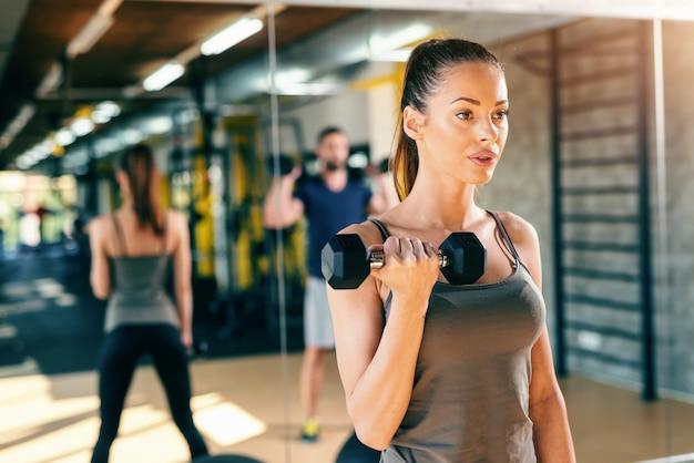Perto da linda morena caucasiana, fazendo exercícios de fitness com halteres. no fundo, seu reflexo no espelho.
